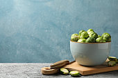 Composition with bowl of brussels sprout on grey table, space for text