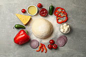 Dough and ingredients for cooking pizza on gray background