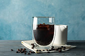 Composition with glass of ice coffee on wooden background