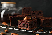 Chocolate cake slices, teapot and almond on wooden background, close up
