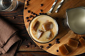 Composition with ice coffee on wooden background, top view