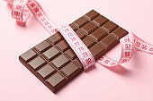 Measuring tape and chocolate bar on pink background