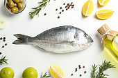 Fresh Dorado fish, spices and cooking ingredients on white background, top view