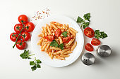 Composition with plate of tasty pasta and ingredients for cooking on white background