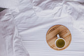 Cup of green tea in bed in cozy wooden house.