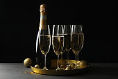 Tray with glasses and bottle of champagne, and baubles on wooden table