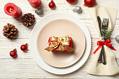 Concept of New year table setting with gift box on wooden table