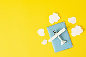 Passport, toy plane and decorative clouds on yellow background, top view