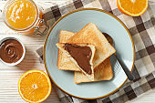 Plate with toasts, orange, jam, choco cream and towel on wood background, top view