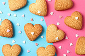 Heart shaped cookies on color background with hearts, top view