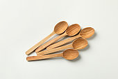 Empty wooden spoons on white background, top view