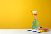 Detergent liquid and cleaning supplies on yellow background, space for text