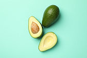 Ripe fresh avocado on mint background, top view