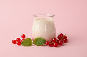 Glass jar of sour cream yogurt and cranberry on pink background
