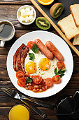 Delicious breakfast or lunch with fried eggs on wooden background, top view