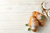 Tasty croissants and cups with coffee on wooden background, top view