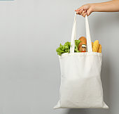 Female hand holds bag with different food on gray background