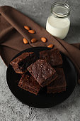 Plate with chocolate cake slices, almond and bottle of milk on grey background, close up