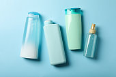 Blank bottles of cosmetics on blue background
