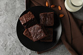 Plate with chocolate cake slices, almond and bottle of milk on grey background, top view