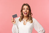 Close-up portrait of excited pretty young blond woman in white dress, holding credit card, showing people how she invests, look camera amused, smiling recommend shopping app, pink background
