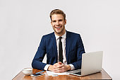 Pleasant charming businessman with blond hair, beard wear suit, sitting office with report, laptop, smiling friendly consulting client, having business conversation with employees, white background