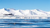 Panoramic view of a glacier and pristine snow covered mountains in Nordfjorden, Svalbard