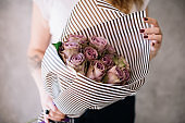 Very nice young woman holding beautiful blossoming elegant mono bouquet of fresh purple roses on the grey wall background