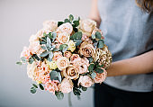 Very nice young woman holding beautiful blossoming wedding bouquet of fresh roses, eustoma, carnations, succulents, flowers in tender cream and pink colours on the grey wall background