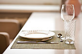 Table setting in a cafe. Elegant empty plate, cutlery, napkin and glasses.