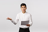 Skeptical and displeased asian male entrepreneur complaining unsatisfied with received documents, shrugging extend hand sideways in dismay, frowning upset, talking to employees