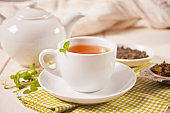 Cup of fresh green or black tea with mint on the white wooden table. Detox and antioxidant drink.