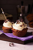 Homemade chocolate cupcakes decorated cheese cream and flowers