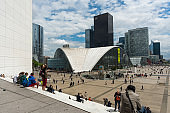 People sitting on the white stairs in front of Grande Arche in La Defense, Paris, France