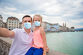 Young dad and daughter in masks taking selfie background famous Fraumunster Church and river Limmat, Switzerland.