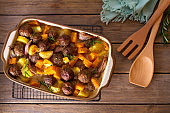Meatballs with pumpkin, potatoes  and herbs in baking dish
