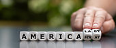 """Hand turns dice and changes the expression """"America first"""" to """"America last""""."""