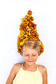 charming smiling child with healthy and strong long blond hair in shape of bonfire with floral arrangement