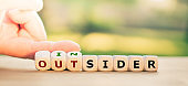 """Hand turns dice and changes the expression """"outsider"""" to """"insider""""."""