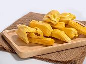 Fresh jackfruit slices on a wood plate.