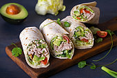 Turkey wraps with avocado, tomatoes and iceberg lettuce on chopping board