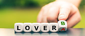 """Symbol for choosing a different lover. Hand turns dice and changes the expression """"Lover A"""" to """"Lover B""""."""
