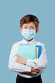 little boy with medical mask, has notebooks and books in hand