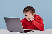 Irritated child boy closing her face with her hands. dressed in red sweatshirt near laptop in studio on blue background