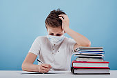 schoolboy siting at the table with medical mask learns lessons,