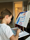 Cute little boy drawing with paints at home