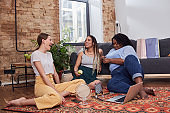 Positive friends spending weekend in home interior