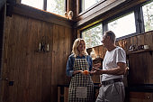 Cheerful man and woman communicating in wooden house