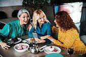 Beautiful smiling ladies using smartphone in cafe