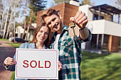 Smiling man and woman holding sold sign and key